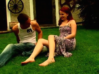 Redhead lassie with admiration copulates on the grass with partner